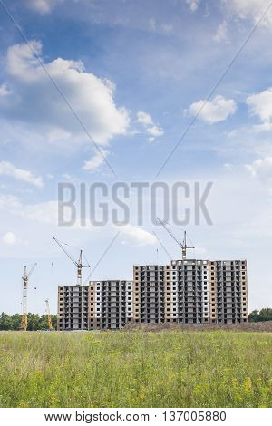 Construction Area In An Open Field Near The Forest On A Background Of Blue Sky With Clouds.