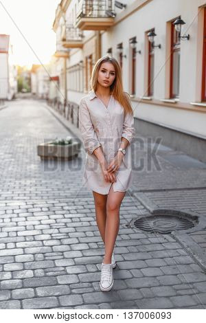 Beautiful Woman In A Stylish Dress And White Sneakers Walking In The City At Sunset.