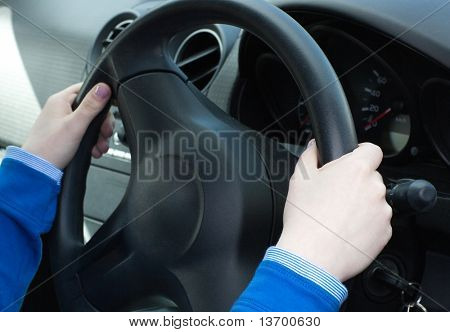 Close-up of woman's hands on the wheel in her car