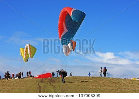 Paragliders preparing to fly from a hill