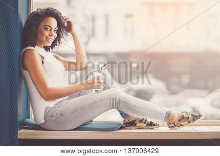 Starting new day with fresh coffee. Happy and merry young African woman posing and smiling at a camera while sitting on the window sill and holding cup with hot drink