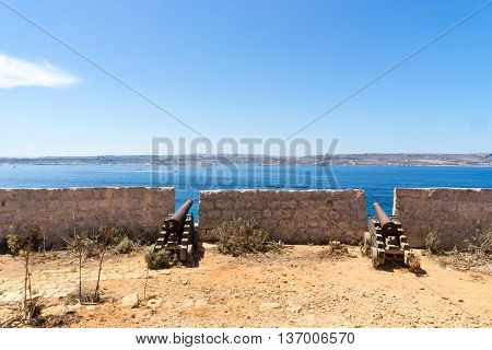 Santa Marija Battery canons on Comino overlooking the mediterranean sea towards Malta