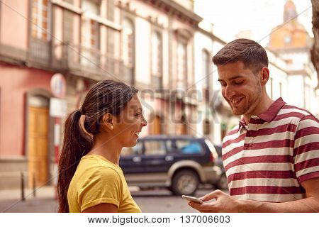 Laughing Young Couple Looking At Cell Phone