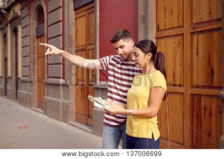 Couple Looking At Map And Pointing