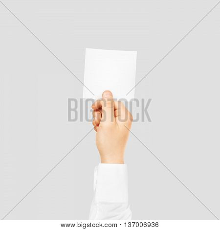 Hand holding square blank white sticker mock up isolated on gray. Sticker mockup holder. Empty paper clue remnder hold in hands.