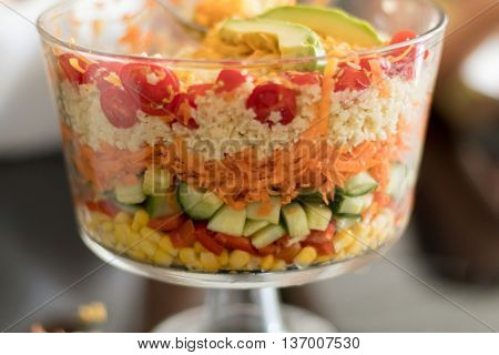 Healthy Multi Layered Salad in a Glass Trifle Bowl on on a glass table top shot with narrow field of focus