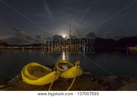Yellow canoes at night, along the Mediterranean Sea, with the moon rising in the background.