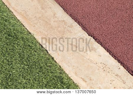 Rubber playpark flooring red rubber wetpour next to concrete and green artificial grass