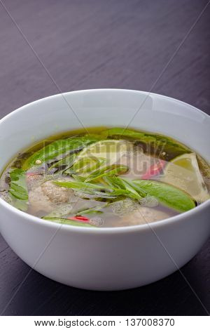 Bowl full of oriental soup with meatballs sweet peas lime chili and chives.