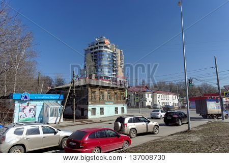 Nizhny Novgorod Russia. - April 07.2016. Old wooden residential two-story house on the street Kovalikhinskaya 100 on a background of high-rise buildings