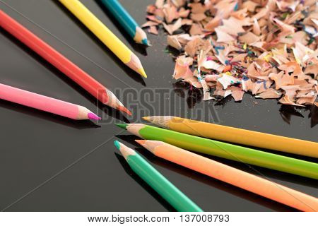 Sharpened colorful pencils and pile of colorful pencil shavings on black glass gloss table with shallow depth of focus
