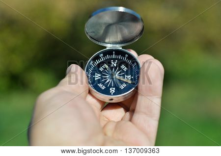 Compass in hand. Open the magnetic compass holds the left hand men.