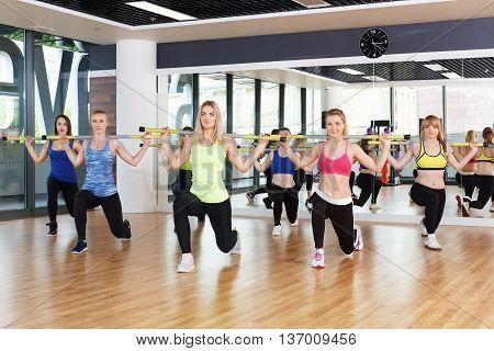 Group of young women in fitness class. Group of people making exercises. Girls do lunges with barbells. Healthy lifestyle, training, sport, gym studio. Girls in fitness club, lunges with weights.