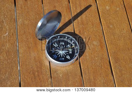 The compass on the boards. Open the magnetic compass lies on the dark wooden boards