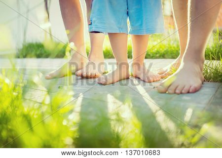 Group of happy children lying on green grass outdoors in summer park