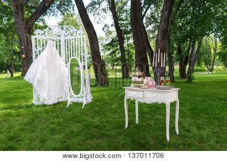 Vintage boudoir in the shade on a beautiful lawn, a wedding dress hangs in front.