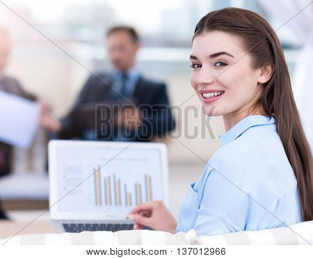 Involved in work. Positive delighted beautiful woman smiling and using laptop while her colleagues sitting in the background