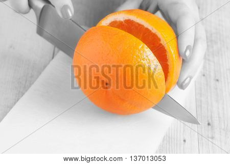 Woman hand cutting orange in two with kitchen knife.