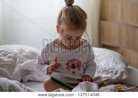 a little girl reads a children's book in bed after sleep