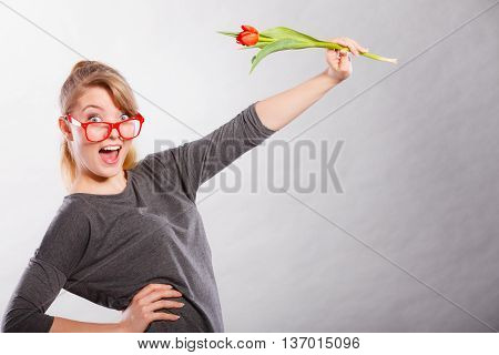 Flora nature beauty fun joy leisure casual fashion concept. Nerdy girl waving flower. Young cheerful smiling lady in glasses holding tulip.