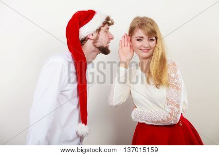Man boyfriend in santa claus hat whispering to woman girlfriend ear. Gossip couple on gray. Christmas xmas season.