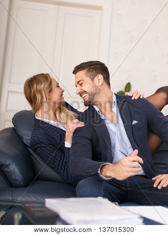 Blonde businesswoman fall behind boss onto sofa seduction