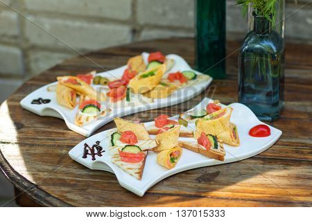 Beautifully decorated catering banquet table, two dishes on a wooden table.