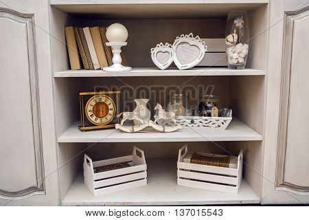 white outdoor small cupboard with trivia books, clock, wooden horses, jars, candle holders, photo frames