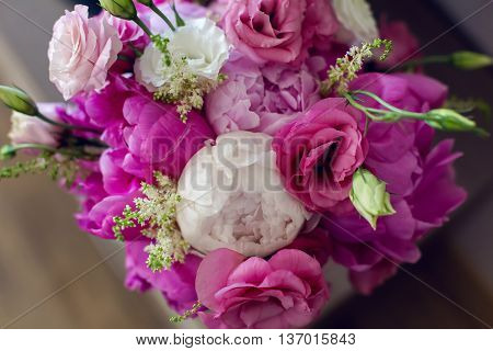 wedding bouquet with peonies and roses lying in the window on the windowsill