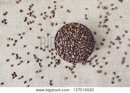 Burlap texture with coffee crop in a bowl background, plenty of robusta beans in plate. Sack cloth canvas with copy space. Scattered seeds at hessian textile, sof toning
