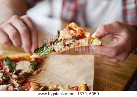 close up of man eating a slice of authentic brick oven fired pizza shot with selective focus