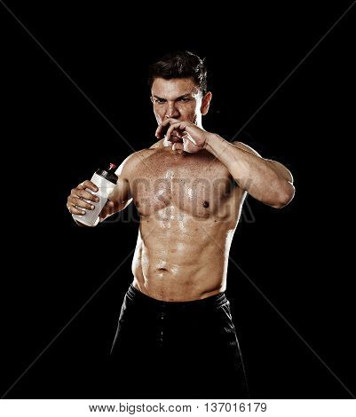 attractive strong sport man drinking water holding bottle sweating tired after training hard on gym bodybuilding workout isolated on black background in health care hydration and fitness concept