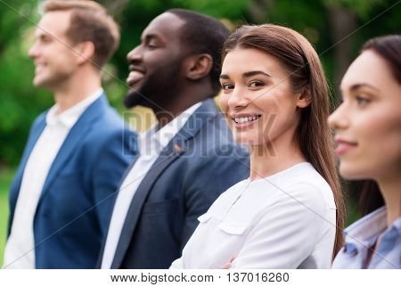 Ready to work together. Cheerful delighted beautiful woman smilin and expressing gladness while standing with her colleagues outside