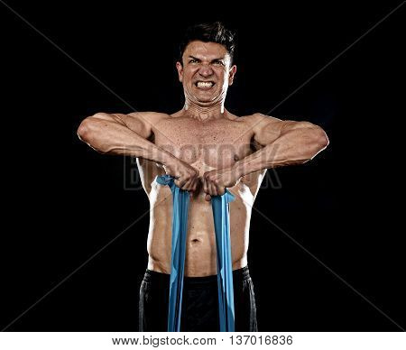 strong fit sport man training hard with elastic rubber band working muscles sweating in body building training workout on gym isolated on black background