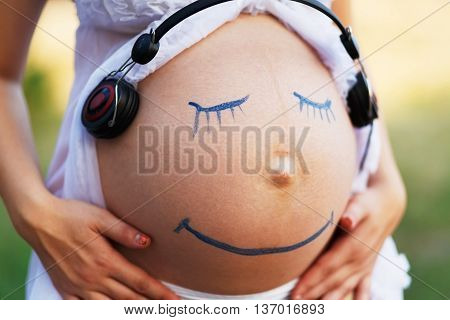 Pregnant woman belly closeup with smiling funny face drawing on it, listening to the music in earphones
