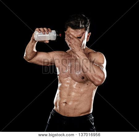 attractive strong sport man pouring water on his face sweating tired after training hard on gym bodybuilding workout isolated on black background in health care hydration and fitness concept