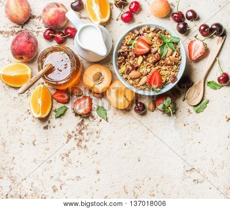 Healthy breakfast ingredients. Oat granola in bowl with nuts, strawberry and mint, milk in jug, honey in glass jar, fruit, berries and mint on light concrete background, top view, copy space, horizontal composition