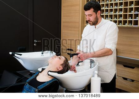 Hairstylist washing head to the young woman at the hairdresser.