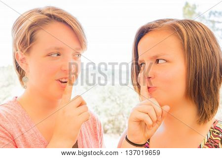 Close up of Two Cute Young Girls Asking for Silence