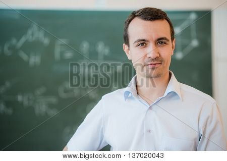 Portrait of young happy smiling teacher man standing near chalkboard background.