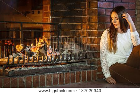 Melancholic pensive woman relaxing resting at fireplace. Thoughtful nostalgic young girl heating warming up. Winter at home.