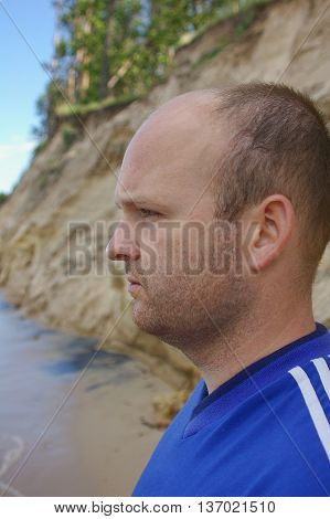 A portrait close up of the Handsome man on nature standing by the ocean. Summer. Young Man Thinking alongshore