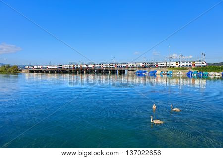 Rapperswil, Switzerland - 7 September, 2015: a train passing the Seedamm. Seedamm is the partially artificial causeway and bridge at the most narrow area of Lake Zurich between the town of Hurden and the city of Rapperswil.
