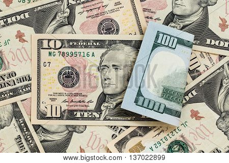 Multitude of banknotes nominal value of ten dollars at front side and nominal value of hundred dollars at reverse side. Concept of potential profitable investments and successful business. Close-up