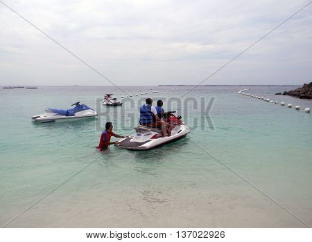 LAPU LAPU, CEBU / PHILIPPINES - JULY 28, 2011: People leave the beach for a ride in a jet ski at Shangri-La's Mactan Resort and Spa.