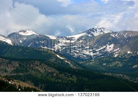 Snow Capped Mountains Above the Tree Line in a Pine Tree Forest