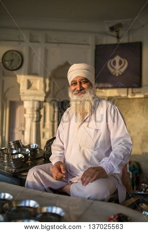 Amritsar, India - March 30, 2016: Portrait of Indian sikh man in turban with bushy beard in Golden temple in Amritsar