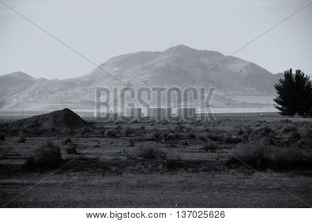 A dump with storage tanks and industrial buildings in the Mojave Desert.
