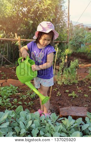 Little girl using watering can water plants in garden montessori education concept