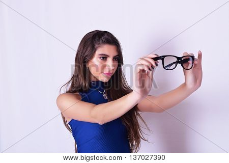 Portrait of fashionable young woman wearing stylish urban clothes holding hipster glasses. Fashion studio portrait over grey backgroung.